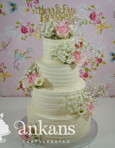 Bröllopstårta med färska rosa rosor och brudslöja